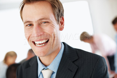 Buy stock photo Closeup portrait of a happy young businessman laughing and his colleagues working behind him