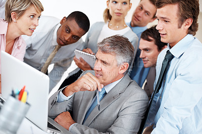 Buy stock photo Senior executive in front of laptop with colleagues surrounding him