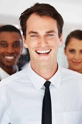 Buy stock photo Portrait of a happy young male business executive with colleagues in background