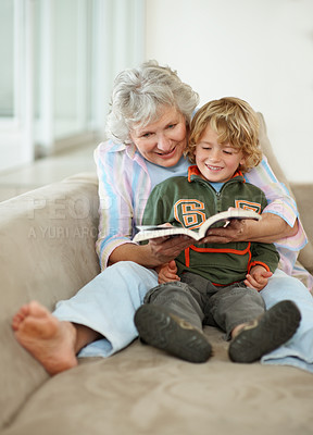 Buy stock photo A senior woman and her grandson reading a book while sitting on the sofa