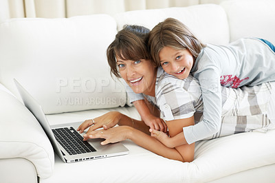 Buy stock photo Portrait of mother and daughter lying on top of each other using laptop and smiling