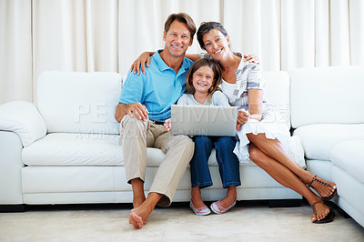 Buy stock photo Portrait of family of three sitting on a sofa using laptop and smiling