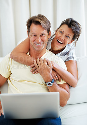 Buy stock photo Man sitting on a sofa using laptop with woman hugging him from behind