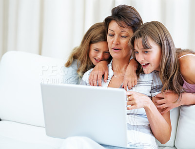 Buy stock photo Woman sitting on a sofa using laptop with daughters watching from behind