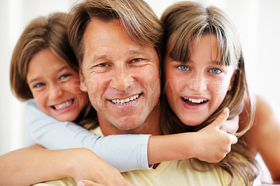 Buy stock photo Closeup portrait of a handsome father with his two daughters smiling over their dad's shoulder