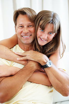 Buy stock photo Man sitting on a sofa with daughter hugging him from behind