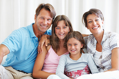 Buy stock photo Portrait of happy family sitting together on a sofa and smiling