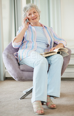 Buy stock photo Portrait of a happy senior woman taking a call on her cellphone while reading a book on the couch