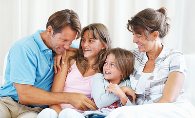 Buy stock photo Family of four sitting on a sofa with man tickling his younger daughter