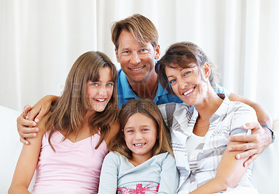 Buy stock photo Portrait of family sitting on a sofa and smiling