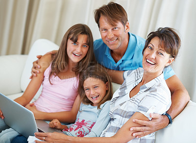 Buy stock photo Portrait of family sitting on a sofa and giving you an attractive smile