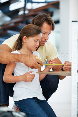 Buy stock photo Man teaching his daughter to use a measuring tape while building a shelf