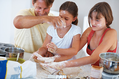 Buy stock photo Two girls rolling dough using rolling pin with father adding flour