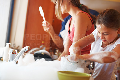 Buy stock photo Focus on young girl washing the dishes with her family