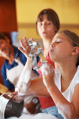 Buy stock photo Young girl drying the gingerbread shaped cookie cutter with her father and sister