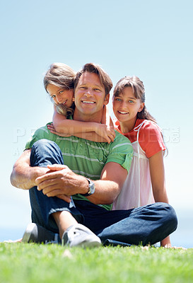 Buy stock photo Full length of man sitting in the grass with his young daughters and smiling