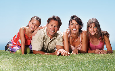Buy stock photo Family of four lying on the grass and smiling