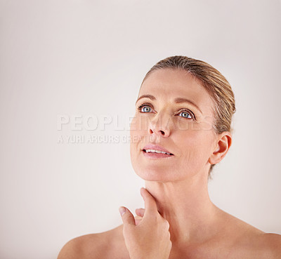 Buy stock photo Cropped studio shot of an attractive mature woman against a light background