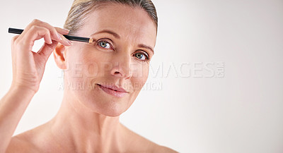 Buy stock photo Cropped studio shot of a mature woman applying eyeliner