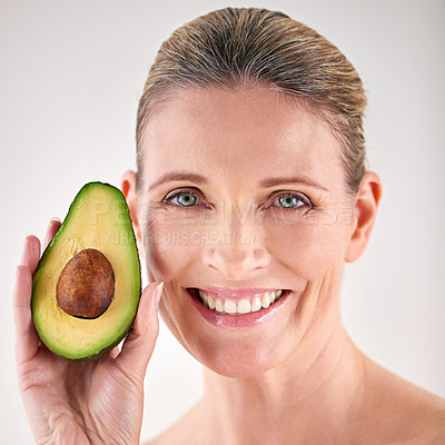 Buy stock photo Cropped studio portrait of a mature woman holding up an avocado