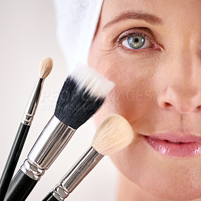 Buy stock photo Closeup studio portrait of a mature woman posing with a set of makeup brushes