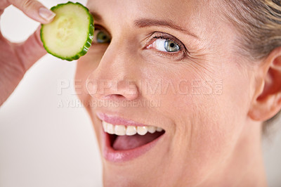 Buy stock photo Cropped studio portrait of a mature woman holding up a slice of cucumber to her eyes