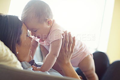 Buy stock photo Shot of a mother holding her baby girl in the air while lying on a sofa