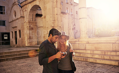 Buy stock photo Shot of a young couple looking at pictures on a camera while walking through an old city
