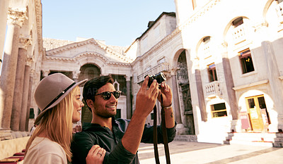 Buy stock photo Shot of a young couple taking pictures while walking through a foreign city