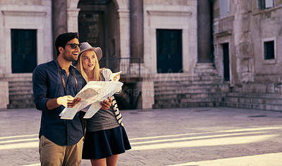 Buy stock photo Shot of a couple looking at a map while walking through an old city