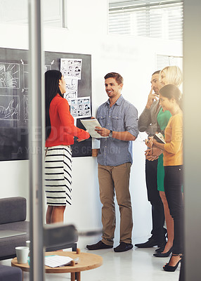 Buy stock photo Full length shot of a group of businesspeople strategizing at the blackboard