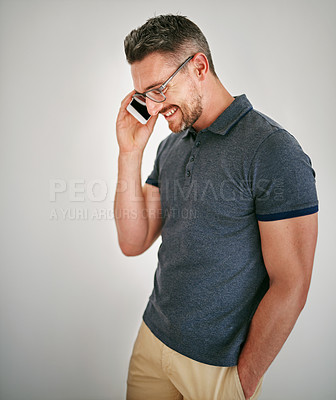Buy stock photo Shot of a man talking on his cellphone against a gray background