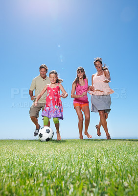 Buy stock photo Low-angle image of a young girl kicking a football as her family chases her