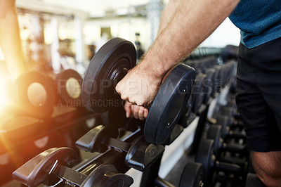Buy stock photo Cropped shot of a man's hands lifting a dumbbell off a rack in a gym