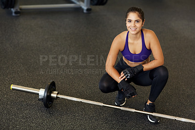 Buy stock photo High angle portrait of a young woman crouching beside a barbell in the gym