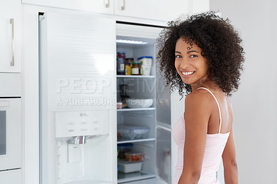 Buy stock photo Portrait of a young woman looking in her fridge