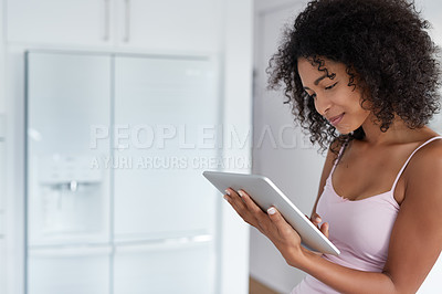 Buy stock photo Shot of a young woman using a digital tablet in her kitchen