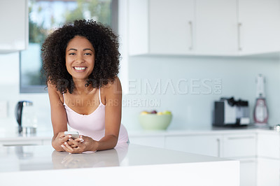 Buy stock photo Portrait of a young woman using a cellphone in her kitchen