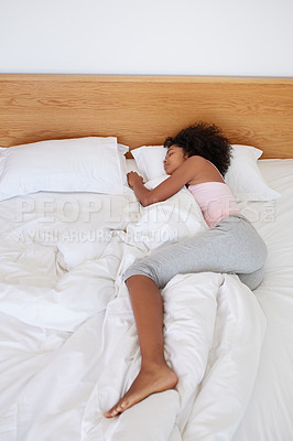 Buy stock photo Shot of a young woman sound asleep in her bed
