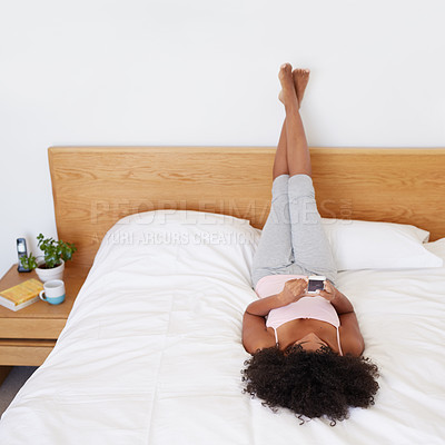 Buy stock photo Shot of a young woman using her cellphone while lying on her bed