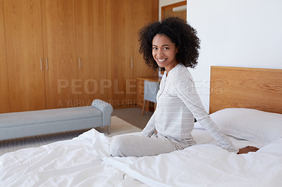 Buy stock photo Portrait of a young woman sitting on her bed