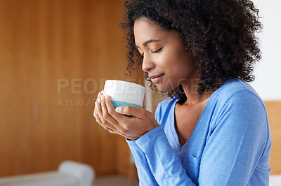 Buy stock photo Shot of a young woman having a cup of coffee at home