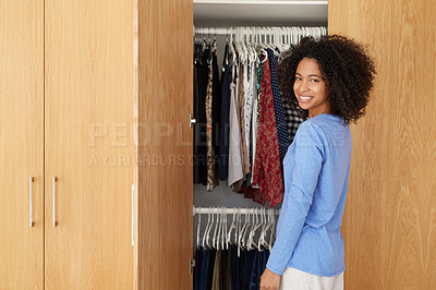 Buy stock photo Shot of a young woman standing by her open bedroom closet