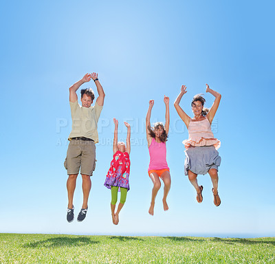 Buy stock photo Family of four having fun outdoors and jumping on the grass