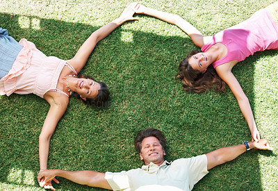 Buy stock photo Top view of family lying on grass holding hands and smiling