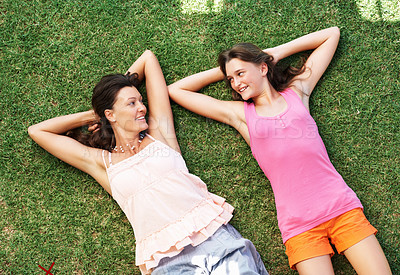 Buy stock photo Top view of mother and daughter relaxing on grass and smiling with hands behind head