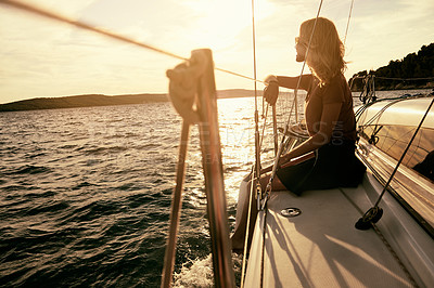 Buy stock photo Shot of a young woman sitting on a yacht