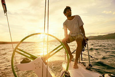 Buy stock photo Shot of a young man relaxing on his yacht