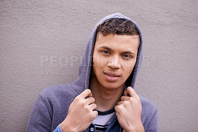 Buy stock photo Portrait of a teenage boy wearing a hoodie standing against a gray wall