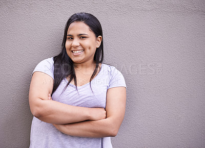 Buy stock photo Portrait of a young woman standing against a gray wall